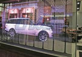pantalla de led transparente para escaparates grandes y fachadas como la de un concesionario de coches. Se muestra el rpoducto de dentor y sus posibilidades en una imagen. Screenad especialista de pantallas de led transparentes en España